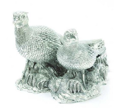 a medium sized silver figurine of a pair of pheasants